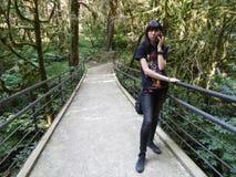 Flicka med telefonanseende på bron i relictdungen Fotografering för Bildbyråer