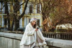 Flicka med telefonen i hand i staden Arkivbilder