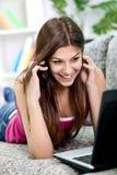 Flicka med telefonen och bärbar dator Arkivfoto