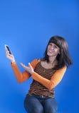 Flicka med telefonen på en blå bakgrund arkivbild
