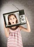 Flicka med televisionen på henne som är head Fotografering för Bildbyråer