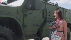 Flicka med tillhörigheter i handhandlagdörr av den militiary bilen och leenden lager videofilmer