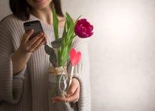 Flicka med tulpan och telefonen i händer Arkivfoton