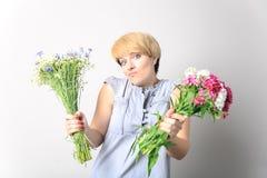 Flicka med två buketter av lösa blommor som poserar i studio lösning val Arkivfoton