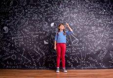 Flicka med två flätade trådar, stor svart tavla med matematiska symboler Royaltyfri Bild