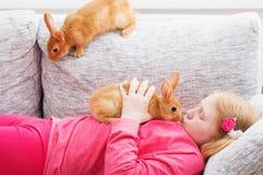 Flicka med två kaniner Arkivfoto