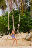 Flicka med två flätade trådar i en baddräkt på en gunga på stranden Arkivbild