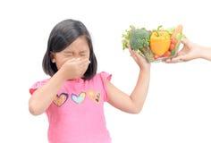 Flicka med uttryck av avsmak mot grönsaker arkivfoto