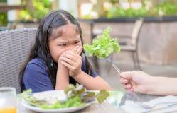 Flicka med uttryck av avsmak mot gr?nsaker arkivfoto