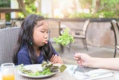 Flicka med uttryck av avsmak mot gr?nsaker arkivbild