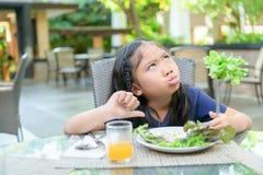 Flicka med uttryck av avsmak mot gr?nsaker royaltyfria bilder