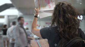 Flicka med väntande på ankomster för lockigt hår i flygplatsen som rymmer ett tecken med namn lager videofilmer