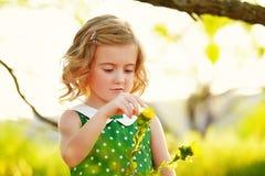Flicka med vårblomman Arkivbild