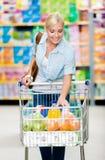 Flicka med vagnen som är full av mat i shoppa royaltyfria bilder