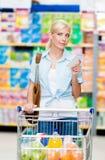 Flicka med vagnen som är full av mat i shoppinggallerian royaltyfria foton