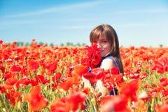 Flicka med vallmor Arkivfoto