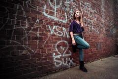 Flicka mot den stads- väggen royaltyfri bild