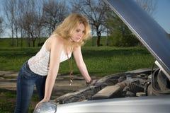Flicka nära bilen med en öppen huv royaltyfria foton