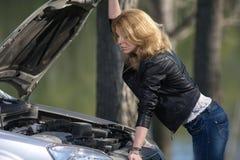 Flicka nära bilen med en öppen huv royaltyfri fotografi