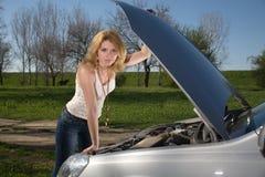 Flicka nära bilen med en öppen huv arkivbilder