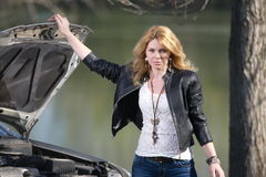 Flicka nära bilen med en öppen huv royaltyfria bilder