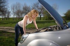 Flicka nära bilen med en öppen huv arkivbild