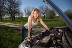 Flicka nära bilen med en öppen huv royaltyfri foto