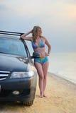 Flicka nära bilen på en sandig strand royaltyfria foton