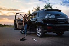 Flicka nära bilen som ser med fasa på locket och taktpinnen av en polis Kvinnlig chaufför som hiting en SNUT Ryssland royaltyfri foto