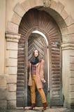Flicka nära den gamla träporten Arkivfoto