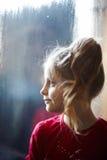 Flicka nära det djupfrysta fönstret Royaltyfria Bilder