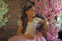 Flicka in nära ett blomningträd Arkivfoton