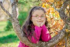 Flicka nära ett träd i parkera Arkivbild