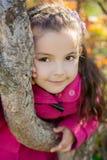 Flicka nära ett träd i parkera Arkivfoto