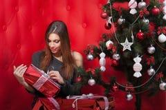 Flicka nära julgranen med gåvor Arkivbilder