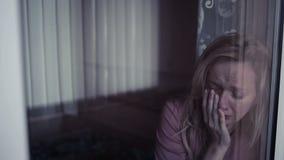flicka nära SAD fönster plachetkvinna revor i schekah stock video