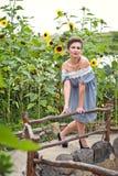 Flicka nära solrosor i en kort klänning 17 Arkivfoton