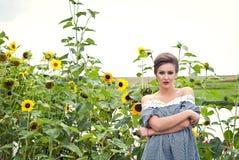 Flicka nära solrosor i en kort klänning 19 Royaltyfri Foto