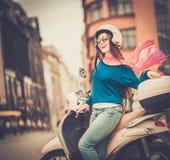 Flicka nära sparkcykeln in i europeisk stad Arkivfoton