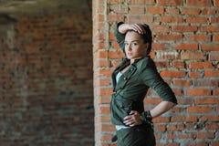 Flicka nära tegelstenväggen i militär stil royaltyfria bilder