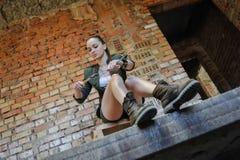 Flicka nära tegelstenväggen i militär stil royaltyfri bild
