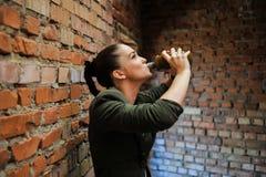 Flicka nära tegelstenväggen i militär stil arkivfoto