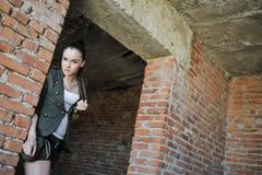 Flicka nära tegelstenväggen i militär stil arkivbilder
