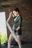 Flicka nära tegelstenväggen i militär stil Lara Croft stil royaltyfri bild