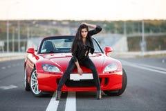 Flicka nära den röda bilen Arkivfoto