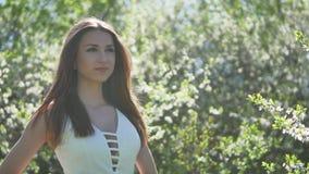 Flicka och blommande körsbär Flickan är den stående livsstilen i naturen som blomstrar den trädgårds- körsbäret arkivfilmer