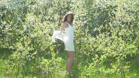 Flicka och blommande körsbär Flickan är den stående livsstilen i naturen som blomstrar den trädgårds- körsbäret stock video