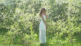 Flicka och blommande körsbär Flickan står i livsstilnaturen som blomstrar den trädgårds- körsbäret stock video