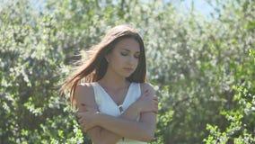Flicka och blommande körsbär Flickan står i naturen som blomstrar den trädgårds- livsstilkörsbäret stock video