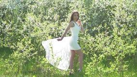 Flicka och blommande körsbär Flickan står i naturlivsstilen som blomstrar den trädgårds- körsbäret arkivfilmer